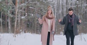 Молодой человек и женщина в пальто имеют потеху и играют со снегом в лесе зимы в замедленном движении Счастье и видеоматериал