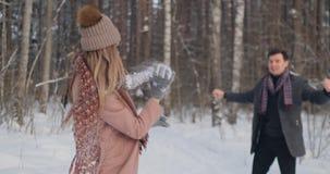 Молодой человек и женщина в пальто имеют потеху и играют со снегом в лесе зимы в замедленном движении Счастье и акции видеоматериалы