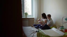 Молодой человек и женщина разговаривая и играя с младенцем сток-видео