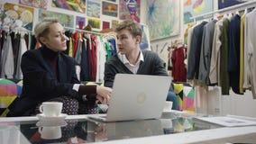 Молодой человек показывает его проект на ноутбуке к взрослой коммерсантке в магазине одежды видеоматериал