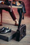 Молодой человек подготавливая чистые отремонтированные ботинки для клиентов стоковое изображение