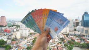 Молодой человек держит в его руках деньги Малайзии на фоне центра города Куалаа-Лумпур видеоматериал