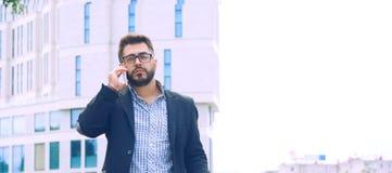 Молодой человек с бородой в стеклах держа кофейную чашку и говоря на мобильном телефоне пока идущ outdoors стоковое фото