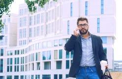 Молодой человек с бородой в стеклах держа кофейную чашку и говоря на мобильном телефоне пока идущ outdoors стоковые фотографии rf