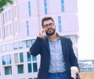 Молодой человек с бородой в стеклах держа кофейную чашку и говоря на мобильном телефоне пока идущ outdoors стоковые фото