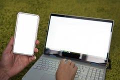 Молодой человек работая на ноутбуке и смартфоне дома Современные ноутбук и мобильный телефон с белыми пустыми экранами Фрилансер  стоковое фото rf