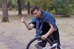Молодой causacian человек с попытками отвертки для того чтобы повредить провод велосипеда на получившемся отказ парке Действия ва стоковое фото rf