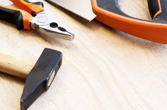 Молоток, ногти и плоскогубцы лежат на деревянной предпосылке Конструкция оборудует выборочный фокус стоковые фотографии rf