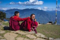2 монаха милых бутанских послушника молодых на верхней части горы, одном поворачивают его голову и улыбки стоковые изображения