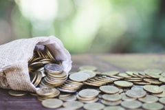 Монетки на открытой полной сумке на деревянном столе с предпосылкой природы, сбережения денег, вклад, растя концепция, штабелируя стоковые фото