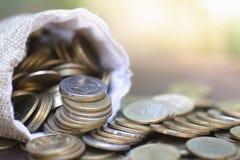 Монетки на открытой полной сумке на деревянном столе с предпосылкой природы, сбережения денег, вклад, растя концепция, штабелируя стоковые изображения rf
