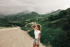 Модная девушка в белых одеждах стоя на дороге в гористых местностях Зеленая трава и горы стоковое фото rf