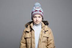 Модный мальчик в outerwear зимы связанный шлем стоковые изображения