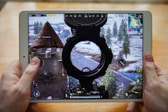 Москва/Россия - 25-ое февраля 2019: Белое ipad в руке На экране чернь игры PUBG стоковое изображение rf