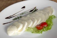 Моццарелла с томатом вишни, зеленым салатом и шлихтой в белой плите на деревянной предпосылке стоковое фото