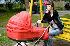 Мother with a baby carriage  on a bench in park Stock Photography