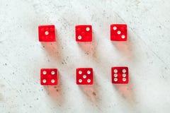 Надземная съемка - красная просвечивающая игра dices показывать все номера от 1 до 6 на белой конкретной доске стоковая фотография