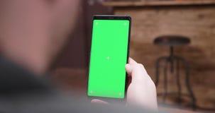 Над съемкой плеча handheld человека смотря телефон с зеленым экраном акции видеоматериалы