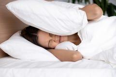 Надоеданная молодая женщина покрывая уши с подушкой, страдая от шума стоковое фото
