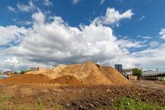 Насыпь грязи на предпосылке голубого неба с белыми облаками стоковое фото rf