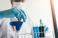 Научный исследователь или пробирка химического вещества доктора лить в лаборатории стоковые изображения