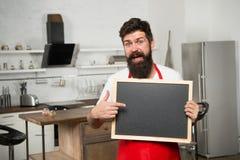 Наше меню ресторана или кафа гостя рекламодателя Шеф-повар человека с доской, космосом экземпляра мужчина возмужалый Бородатый по стоковое изображение rf