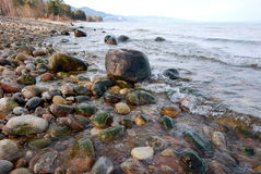 На берегу Байкала возле поселка Мурино. The pebbly shore of the lake is punctuated by large boulders, which give a certain charm Stock Photos