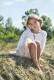На сене сидит маленькая девочка и быть грустный стоковое изображение
