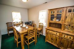 Небольшая комната с таблицей, стульями, деревянным Hutch и компьютером стоковая фотография