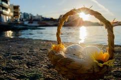 Небольшая корзина с 2 пасхальными яйцами на море doc на золотом часе стоковое изображение rf