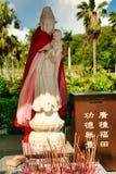 """Небольшая статуя богини Guanyin с младенцем в ее оружиях в парке Nanshan Маленькая коробка говорит: """"для пожертвований """"Хайнань стоковые изображения"""