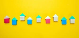 Небольшие деревянные модели дома блоков с крышами на желтой предпосылке стоковые фотографии rf