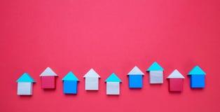 Небольшие деревянные модели дома блоков с крышами на красной предпосылке стоковое изображение rf