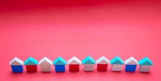 Небольшие деревянные модели дома блоков с крышами на красной предпосылке стоковая фотография