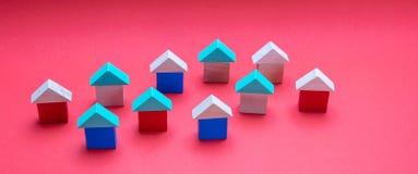 Небольшие деревянные модели дома блоков с крышами на красной предпосылке стоковая фотография rf