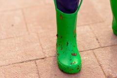 Небольшой зеленый цвет childs welly предусматриванный в грязи и листьях стоковое изображение rf