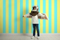 небольшой ребенок хочет летать самолет нося шлем самолета стоковые фото