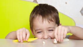 Небольшой ребенок отливает от пластилина диаграмму в форму на конце таблицы вверх Портрет мальчика показывая эмоции: счастье, пот акции видеоматериалы
