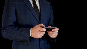Неизвестный бизнесмен в костюме на черной предпосылке Человек держит смартфон и касается экрану телефона с его акции видеоматериалы