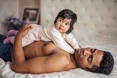 Немногое младенец лежа на ее спать папе стоковое изображение rf