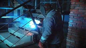 Непознаваемый человек в защитной одежде и маске на фабрике конструкции приниманнсяая за сваривая работа Концепция  сток-видео