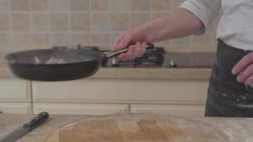 Непознаваемый человек в форме шеф-повара кладет соль в лоток fryng и бросает вверх мясо в skillet Профессиональный варить повара сток-видео