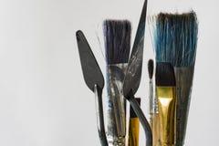 Несколько щеток и 2 шпателя для художника на белой предпосылке Щетки и шпатели имеют различные размеры стоковые фотографии rf