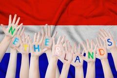 Нидерландская надпись на руках детей на фоне развевая флага Нидерланд стоковое фото rf