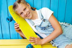 Нappy, laughing child wearing cool fashion clothing posing with colorful skateboard against blue wall, urban style royalty free stock photography