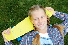 Нappy, laughing child wearing cool fashion clothing posing with colorful skateboard against green grass, urban style royalty free stock images