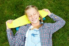 Нappy, laughing child wearing cool fashion clothing posing with colorful skateboard against green grass, urban style stock photo