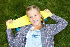 Нappy, laughing child wearing cool fashion clothing posing with colorful skateboard against green grass, urban style stock image