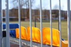 Новые стойки на футбольном поле конструкции металла светлой с пластиковыми местами в голубом и желтом Места для вентиляторов в ст стоковые фото