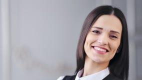 Новое лицо конца-вверх усмехаясь красивой кавказской коммерсантки представляя и смотря камеру сток-видео